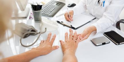 Reumatolog Primula Clinic badająca dłonie starszej kobiecie