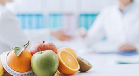 Owoce na stole i rozmawiający lekarze w tle