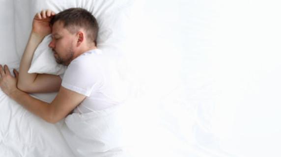 Mężczyzna śpiący pod białą pościelą