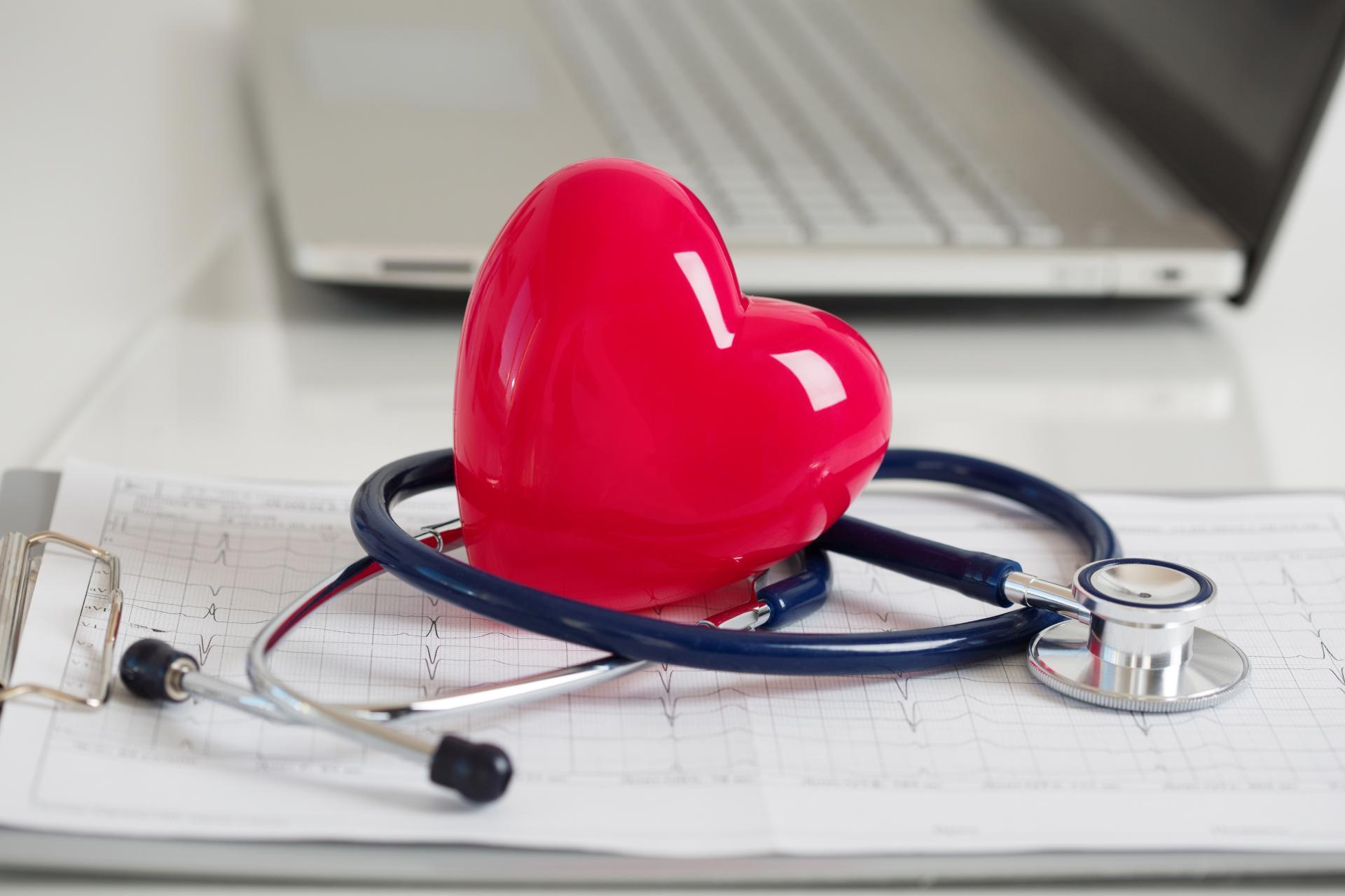 Plastikowe czerwone serce leżące obok profesjonalnego sprzętu lekarskiego
