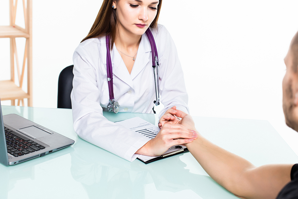 Młody mężczyzna podczas wizyty u doktora, który mierzy mu ciśnienie